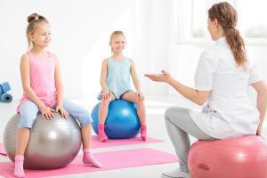 Young physiotherapist explaining exercises to smiling school girls sitting on exercise balls