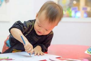 Cute little Asian boy coloring with a pencil