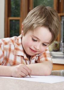 Young boy writing with pencil